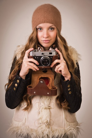 Fashionable young girl with old camera in the hand photo