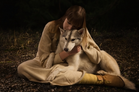 cosplay: Slavonian girl in the traditional suit and siberian husky in the deep forest