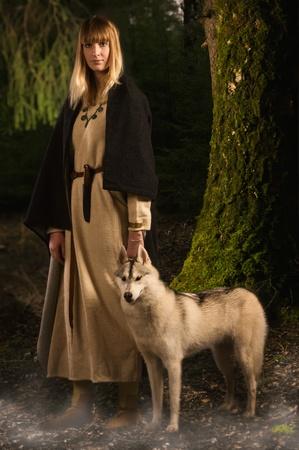 medieval dress: Chica eslava en el traje tradicional y husky siberiano en el bosque profundo