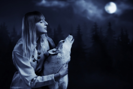 Slavonian girl in the traditional suit and gey wolf in the deep forest photo