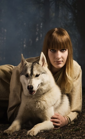 russian woman: Slavonian girl in the traditional suit and siberian husky in the deep forest