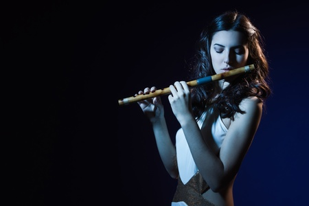 Sensuality beauty brunette plays a wooden flute Stock Photo - 16891307