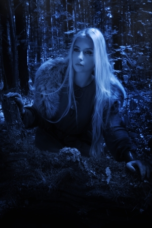 Scandinavian girl in the night dark forest photo