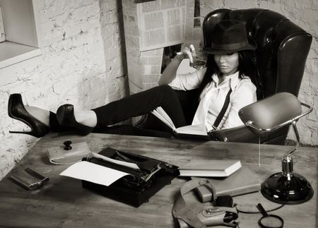 Retro detective girl sits at a table in the agency Stock Photo - 17449919