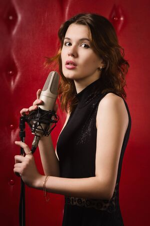 An elegant female singer with microphone photo