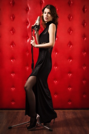 An elegant female singer with microphone Stock Photo