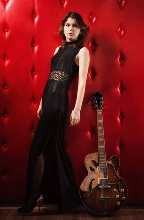 Elegant woman in black with electric guitar photo
