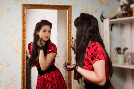 Attractive pin-up girl in front of the mirror photo