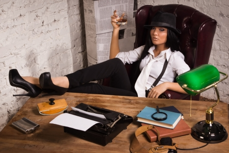 Retro detective girl sits at a table in the agency Stock Photo - 17457924