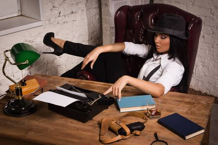 Retro detective girl sits at a table in the agency Stock Photo - 17457933