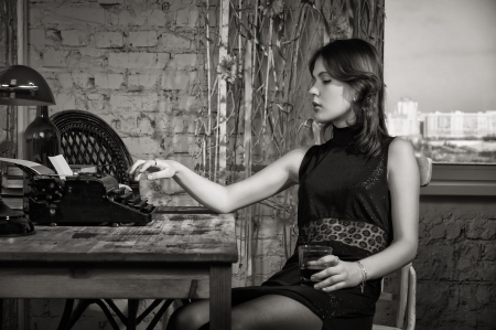 Elegant woman in black at the table with the old typewriter 스톡 콘텐츠