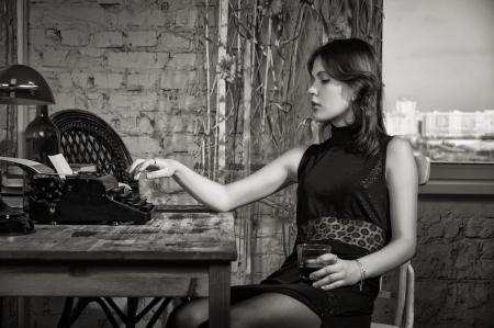escribiendo: Mujer elegante en negro en la mesa con la vieja m�quina de escribir Foto de archivo