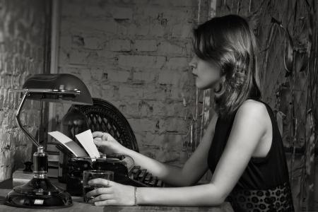 エレガントな黒い服の女性は古いタイプライターとテーブルで