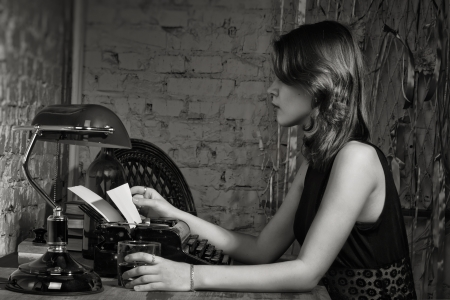 the author: Elegant woman in black at the table with the old typewriter