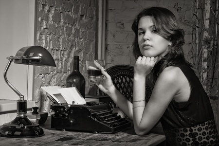 Elegant woman in black at the table with the old typewriter Stock Photo