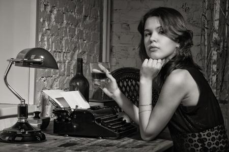 Elegante vrouw in het zwart aan de tafel met de oude schrijfmachine
