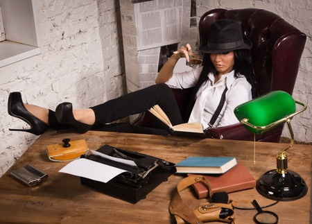 Retro detective girl sits at a table in the agency Stock Photo - 17498440