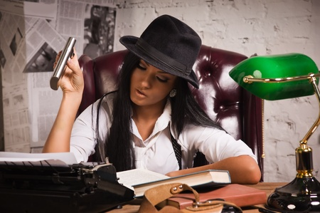 detective agency: Retro detective girl sits at a table in the agency