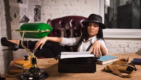 Retro detective girl sits at a table in the agency Stock Photo - 17498495
