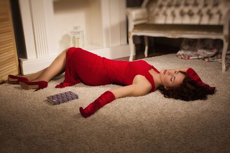 Fashionable lady in a red dress lying on the floor in the vintage interior photo