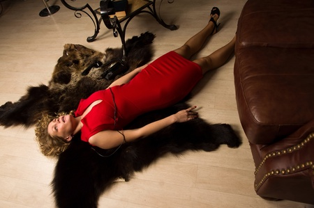 Crime scene simulation: lifeless blonde in the red dress lying on the floor