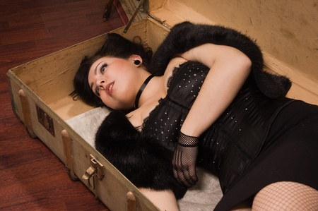 Pretty victim lying in the suit-case photo