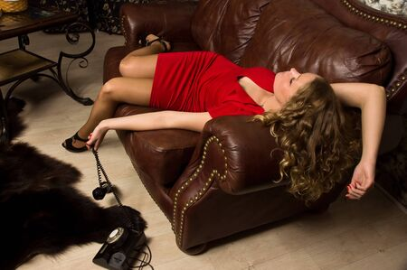 Crime scene simulation: lifeless blonde in the red dress lying on the sofa photo