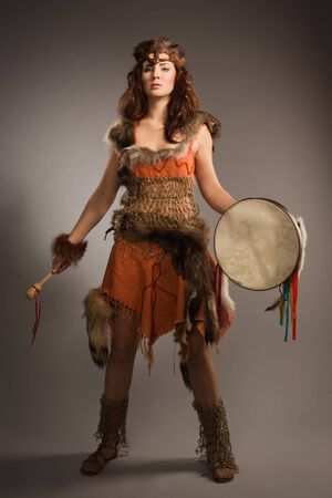 Portrait of shaman woman with a tambourine in studio photo
