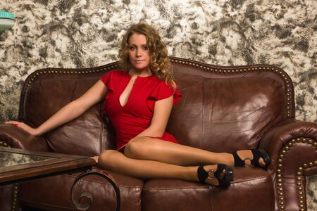Attractive blonde sitting on the couch  in the vintage interior photo