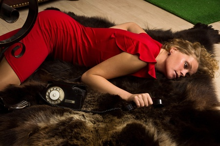 Crime scene simulation: lifeless blonde in the red dress lying on the floor Stock Photo