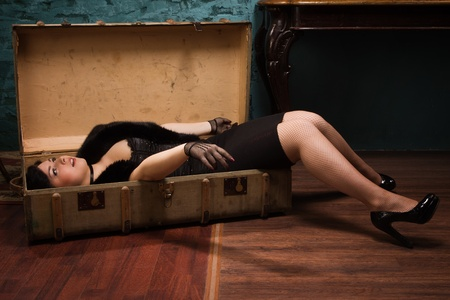 Crime scene in a vintage style. Pretty victim lying in the suit-case Stock Photo - 18411752