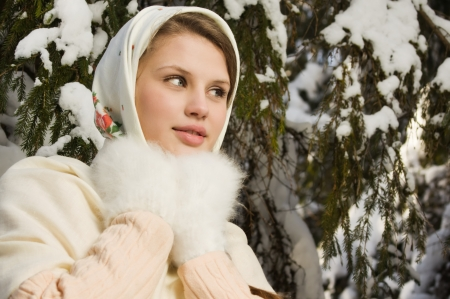 Russian beautiful girl in a traditional dress in the winter forest photo