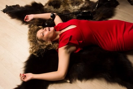 killings: Crime scene simulation: lifeless blonde in the red dress lying on the floor Stock Photo