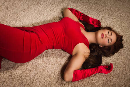 Fashionable lady in a red dress lying on the floor in the vintage interior Stock Photo - 18497185