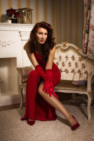 Beautiful brunette in a red dress sitting on the couch  in the vintage interior