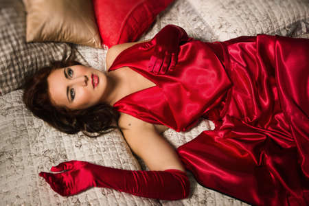 Attractive sensual brunette in a red dress lying on the bed photo