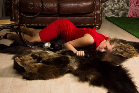 Crime scene simulation: lifeless blonde in the red dress lying on the floor photo