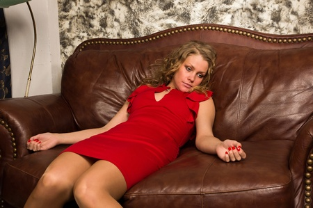 homicide: Crime scene simulation: lifeless blonde in the red dress lying on the sofa