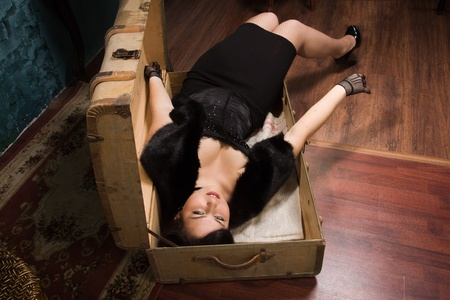 corpse: Crime scene in a vintage style. Pretty victim lying in the suit-case