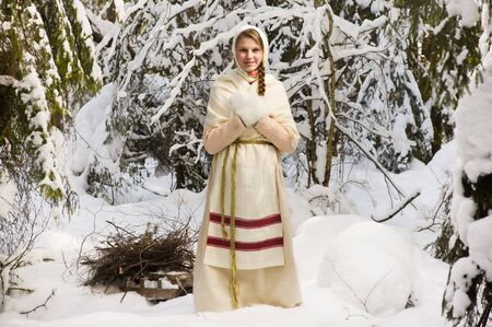Russian girl with a sled in the winter forest photo