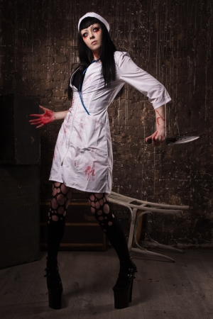 Crazy dead nurse with knife in the hand in a dark room Stock Photo