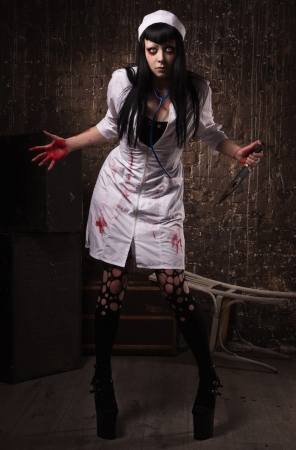psychotic: Crazy dead nurse with knife in the hand in a dark room Stock Photo