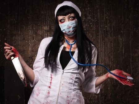 Crazy dead nurse with knife in the hand in a dark room photo