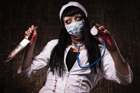 madness: Crazy dead nurse with knife in the hand in a dark room Stock Photo