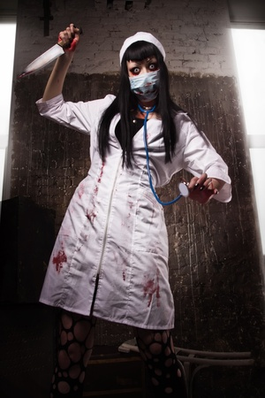 abhorrence: Crazy dead nurse with knife in the hand in a dark room Stock Photo