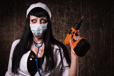 psychotic: Crazy dead nurse with electic drill in the hand in a dark room Stock Photo
