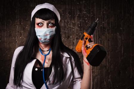 Crazy dode verpleegster met eclectische boor in de hand in een donkere kamer
