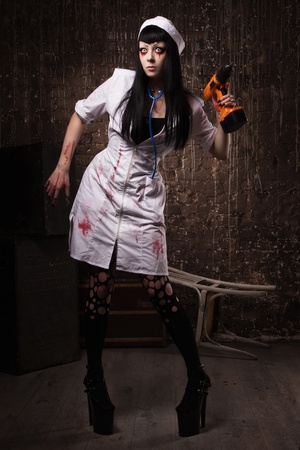 Crazy dead nurse with electic drill in the hand in a dark room photo