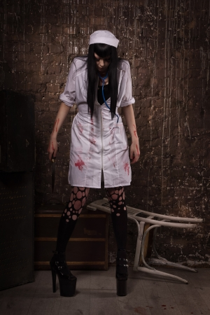 bloodied: Crazy dead nurse with knife in the hand in a dark room Stock Photo