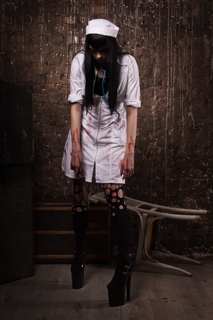 sadistic: Crazy dead nurse with knife in the hand in a dark room Stock Photo